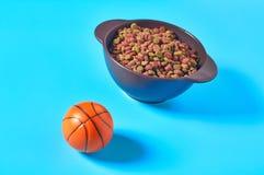 Ceramic bowl full of dry food for pet near basketball ball on blue background
