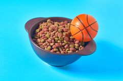 Ceramic bowl full of dry food for pet and basketball ball on blue background