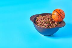 Ceramic bowl full of dry food for pet and rubber basketball ball on blue background