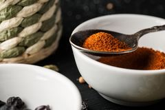 Ceramic bowl with ground paprika and metal spoon above it.  royalty free stock images