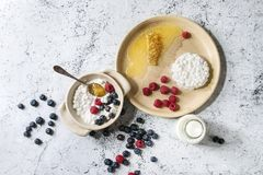 Homemade cottage cheese. Ceramic bowl of homemade cottage cheese served with blueberries, raspberries, bottle of milk and honeycombs over white marble texture Stock Image