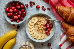 Ceramic bowl of oatmeal porridge with banana, fresh cranberries and walnuts royalty free stock photo