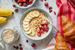 Ceramic bowl of oatmeal porridge with banana, fresh cranberries and walnuts stock photos