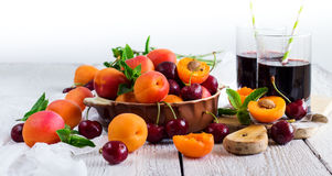Ceramic bowl with organic ripe apricots cherries and juice. Food and drink, healthy nutrition concept. Ceramic bowl with organic ripe apricots and cherries and royalty free stock images