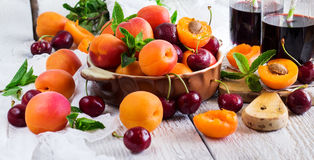 Ceramic bowl with organic ripe apricots cherries and juice Royalty Free Stock Photos
