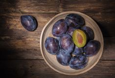 Ceramic bowl with plums over dark wooden board. Fruit background. Top view. Agriculture, Gardening, Harvest Concept. royalty free stock photo