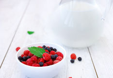 Ceramic bowl with raspberries and blueberries. Ceramic white bowl filled with fresh raspberries and blueberries.Mint leaf as ornament.Glass of milk in the Stock Photo