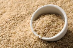 Ceramic bowl with raw brown rice. On cereal stock photo