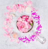 Ceramic bowl with rpnk roses and water,jars of cream,and glass bottle on gray marble table. Spa background Royalty Free Stock Photos