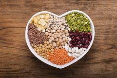Heart-shaped bowl full of types of dry legumes. Ceramic bowl in the shape of a heart full of different types of dry legumes stock photography