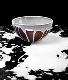 Ceramic bowl and spilled milk in black Stock Photos