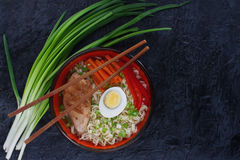 Ceramic bowl of traditional asian ramen soup with noodles, spring onion, chicken, sliced egg, served with wooden chopsticks Stock Photo