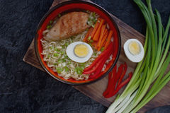 Ceramic bowl of traditional asian ramen soup with noodles, spring onion, chicken, sliced egg, served with wooden chopsticks Royalty Free Stock Image