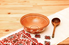 Ceramic bowl and wooden spoon. On a white towel with the ukrainian ornament Stock Photos