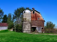 A Ceramic Brick Barn and a Cement Silo. This is a Fall picture of an old style big ceramic brick barn and a cement silo on a family farm located in Winnebago royalty free stock image