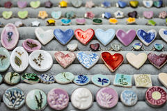 Ceramic brooch in the form of a heart. Ceramic brooches are covered with multi-colored glaze Royalty Free Stock Photography