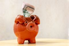 Ceramic brown piggy bank with 50 US dollar bill on a light background.  stock photo