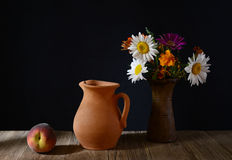 Ceramic carafe, peaches and flowers in a vase Royalty Free Stock Image