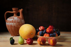 Ceramic carafe and various fresh fruits Stock Photos