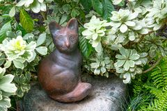 Ceramic cat doll sitting decorative in the park. Background stock photos