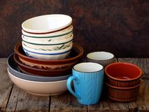 Ceramic, clay empty handmade bowl, dishes and cup on wooden background. Different pottery earthenware utensil, kitchenware. Royalty Free Stock Image