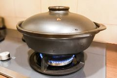 Ceramic clay pot on gas fire generated stove. Not suitalbe material as clay is porous Stock Photo