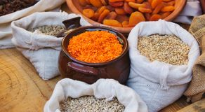 Ceramic clay pot with red lentils and sacks of legumes and grains in a food market stand royalty free stock photo
