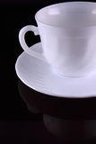 Ceramic coffee cup. With a saucer on dark glass Royalty Free Stock Photo