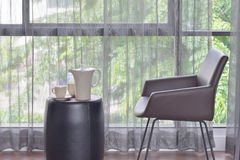 Ceramic coffee set on top of table with dark brown leather chair Stock Image