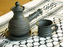Ceramic coffeepot and cup on a white keffiyah scarf. Stock Images
