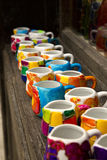 Ceramic colorful cups. Coloured ceramic cups, haind painted on a market shelf Stock Photo