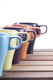 Ceramic Colorful Mugs. On table with 5 different colors in close up Royalty Free Stock Photos