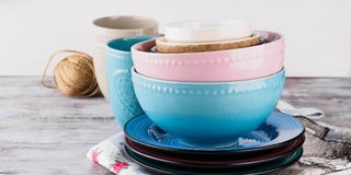 Ceramic crockery on wooden background. Ceramic crockery tableware on wooden background. Pastel vintage color bowls, dishes, cups Royalty Free Stock Photos