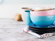 Ceramic crockery on wooden background. Ceramic crockery tableware on wooden background. Pastel vintage color bowls, dishes, cups Stock Photos