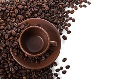 Ceramic Cup And Saucer Stands On Scattered Coffee Beans Isolated On White Royalty Free Stock Image