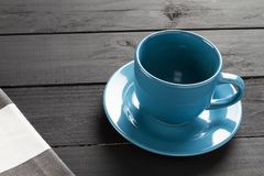 Ceramic cup for coffee of blue color without liquid on black wooden background and rag of gray and white stripes stock images