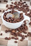 Ceramic cup with coffee seed and euro coins Royalty Free Stock Image
