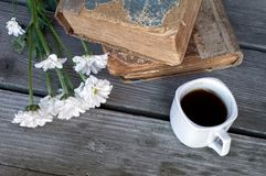 Ceramic cup with coffee with two ancient books lying on a table. Closeup Ceramic cup with coffee with two ancient books lying on a table of old boards with royalty free stock image