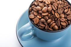 Ceramic cup filled with roasted coffee beans. Isolated on a white background Stock Photo