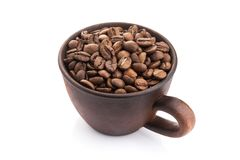 Ceramic cup filled with roasted coffee beans. Isolated on a white background Royalty Free Stock Images