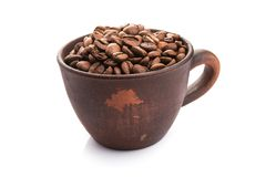 Ceramic cup filled with roasted coffee beans. Isolated on a white background Royalty Free Stock Image