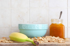 Ceramic cup, fruit and jam, cereal flakes. A composition with a ceramic cup, a banana, some cereal flakes and a jar of jam with a spoon, inside a kitchen, space Stock Photos