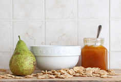 Ceramic cup with a pear and jam, space for text. A composition with a yellow ceramic cup, a pear, some cereal flakes and a jar of jam with a spoon, on a wooden Stock Photography