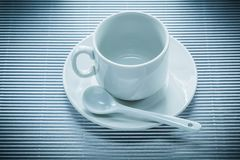 Ceramic cup saucer teaspoon on striped background.  Stock Photo