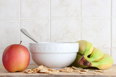 Ceramic cup, some fruit, cereal flakes. A composition with a ceramic cup with a spoon, an apple, some bananas and some cereal flakes, inside a kitchen, space for Royalty Free Stock Images