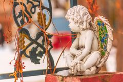 Ceramic Angel Child Sitting on the Wall. Ceramic cupid angel with stained glass in the wings sitting on a brick column beside an iron fence royalty free stock images