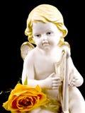 Ceramic cupid and tea rose on black Royalty Free Stock Image