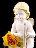 Ceramic cupid and tea rose on black Royalty Free Stock Photos