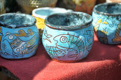 Ceramic cups and bowls with funny drawings. Clay pots and jugs for sale Stock Photos