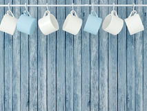 Ceramic cups on hooks. Ceramic cups hanging on hooks in front of wooden blue wall Royalty Free Stock Photography